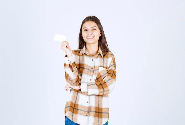 Портрет очаровательной девушки с пустой визитной карточкой, стоящей на белой стене.