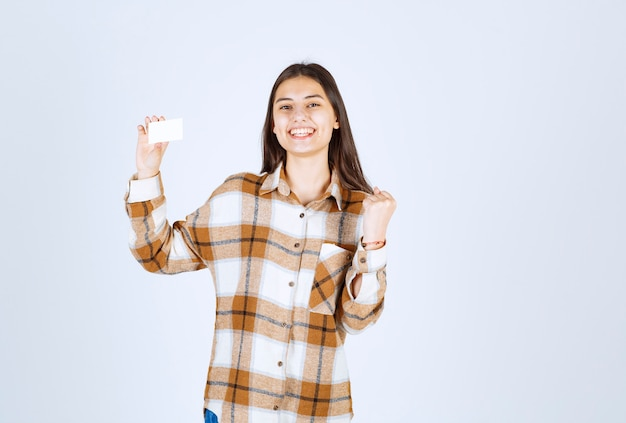 白い壁に立っている空白の名刺を持つ愛らしい少女の肖像画。