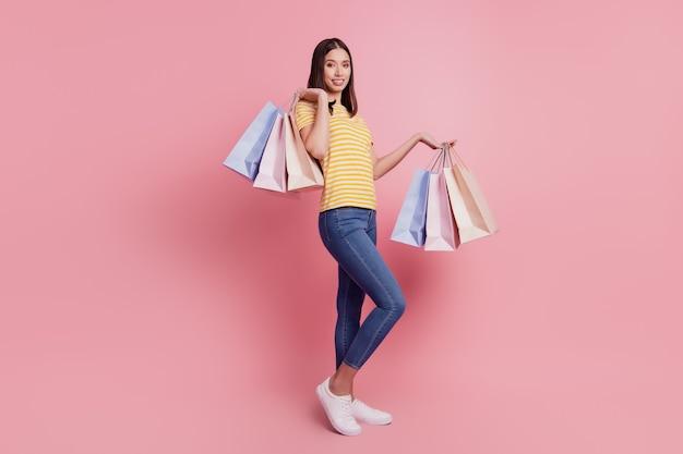 愛らしいゴージャスな若い女性の肖像画は、ピンクの背景にカメラを見てショッピングパッケージを保持します
