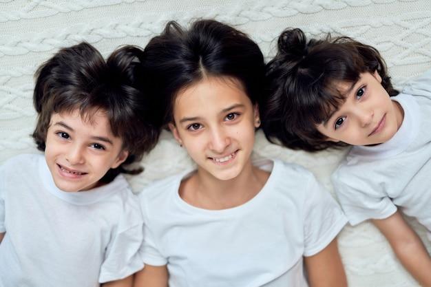 사랑스러운 라틴 어린이, 10대 자매, 어린 형제들이 집에서 침대에 누워 함께 즐겁게 지내면서 카메라를 보며 웃고 있는 초상화. 어린이, 행복, 가족 개념