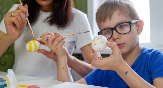 彼のお母さんとイースターエッグを描いている愛らしい小さな男の子の肖像画。