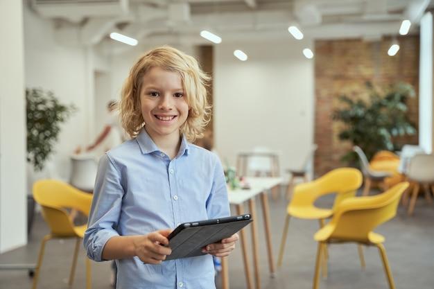 교실에서 포즈를 취하는 동안 태블릿 pc를 사용하여 카메라를 보고 웃고 있는 사랑스러운 어린 소년의 초상화