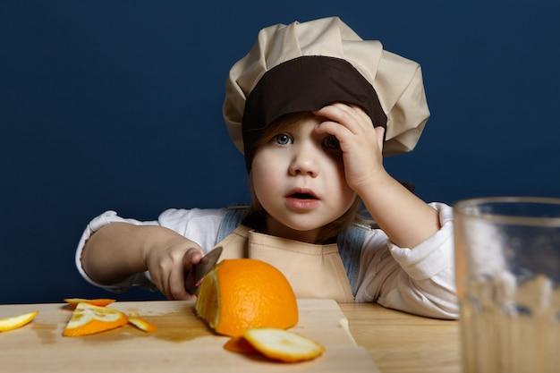 Портрет очаровательной маленькой девочки в головном уборе шеф-повара и фартуке, режущей апельсины на кухонной доске, используя нож, делая свежий сок цитрусовых или здоровый завтрак. витамин, свежесть, диета и концепция питания