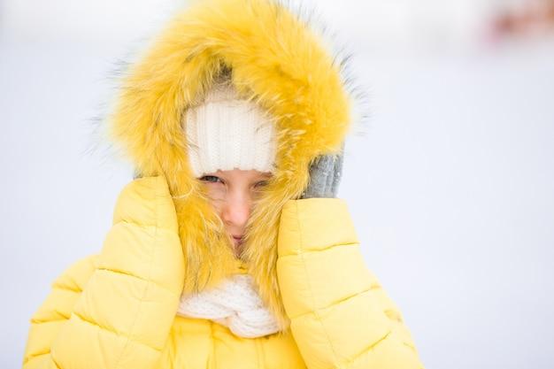 Портрет очаровательны маленькая девочка в зимний снежный день на открытом воздухе