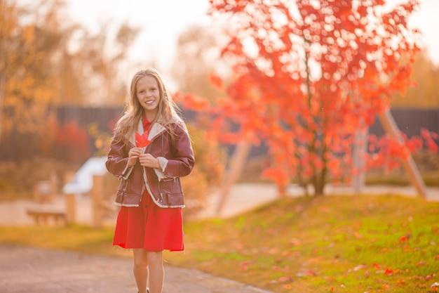 黄色とオレンジ色の愛らしい少女の肖像画は美しい秋の日に屋外で花束を残します