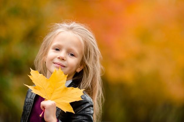 Портрет очаровательны маленькая девочка с желтыми листьями букет осенью на скутере