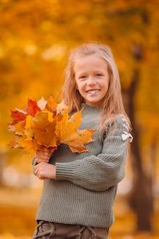 黄色の愛らしい少女の肖像画は秋に花束を残します