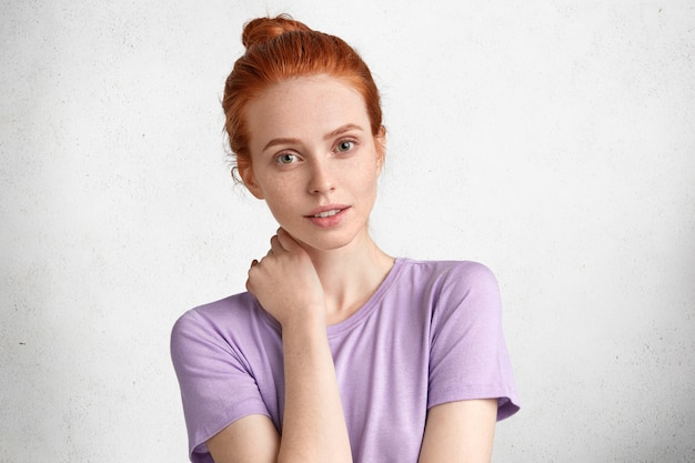 Портрет очаровательной милой молодой женщины с узлом рыжих волос, одетой в повседневную футболку, позирует на фоне белой бетонной стены, выглядит загадочным.