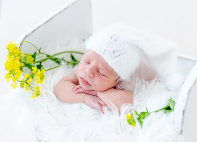 사랑스러운 갓난 아기의 초상화는 배 위에서 자고 노란색 꽃이 있는 흰색 나무 침대에서 뺨 아래 손을 잡고 있습니다. 니트 모자 낮잠을 입고 귀여운 유아 아이