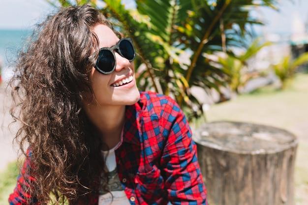 사랑스러운 예쁜 여자의 초상화는 선글라스를 착용하고 해변에서 재미 있습니다. 그녀는 몽환적으로 멀어지고 휴가를 즐깁니다.