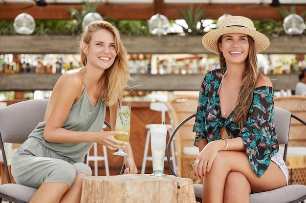 夏のコスチュームで愛らしいリラックスした女性の肖像画。カフェで彼女の親友と会い、新鮮なコールドカクテルを楽しみ、幸せそうな顔つき、ゴシップ、何かについて話してうれしい。夏のパーティーの女性