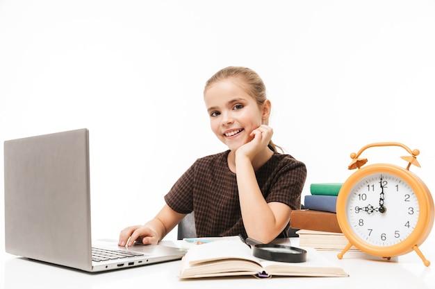 白い壁に隔離されたクラスで本を勉強して読んでいる間銀のラップトップを使用して愛らしい女子高生の肖像画