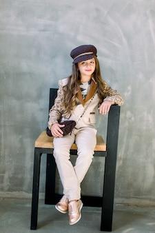 Портрет очаровательной улыбающейся маленькой девочки в легком костюме, золотых кроссовках и шляпе, изолированных на сером сидящем на стуле