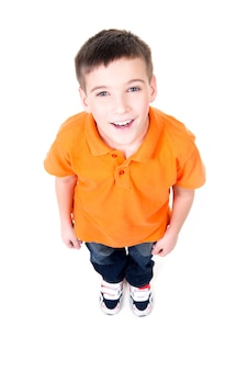 オレンジ色のtシャツで見上げる愛らしい若い幸せな少年の肖像画。上面図。白い背景で隔離。