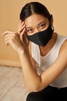 ポーズをとっている間安全にとどまる黒い顔のマスクを身に着けている愛らしい若い混血の女性の肖像画