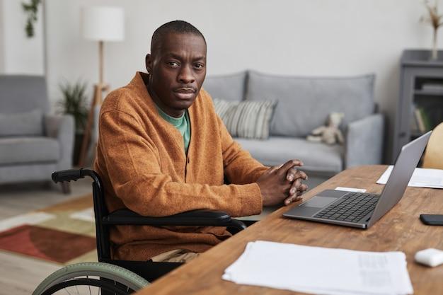 自宅で仕事をし、カメラを見ながら車椅子を使用している大人のアフリカ系アメリカ人男性の肖像画、コピースペース