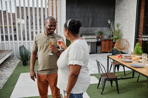 屋外テラスで飲み物を楽しんで、幸せそうに笑っている大人のアフリカ系アメリカ人のカップルの肖像画コピー...