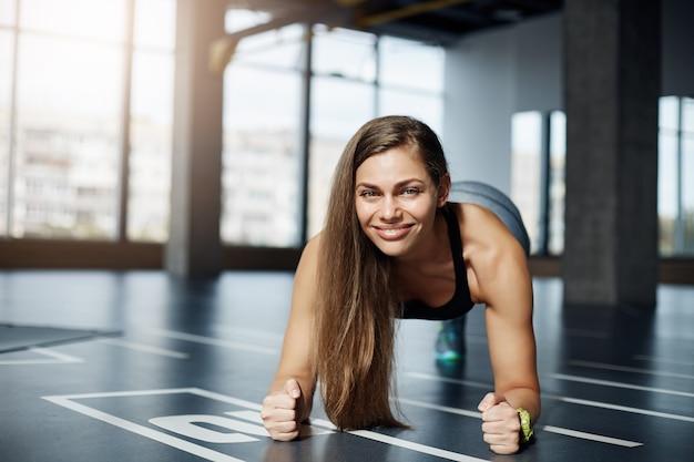 体育館の床で肘板運動をしている大人の美しい女性の肖像画。健康的なフィットネスボディのコンセプト。