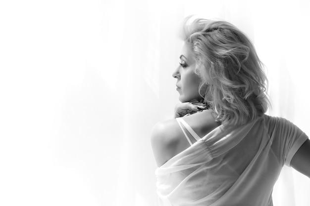 窓を見て、何かを考えている大人の金髪女性の肖像画。黒と白の写真。