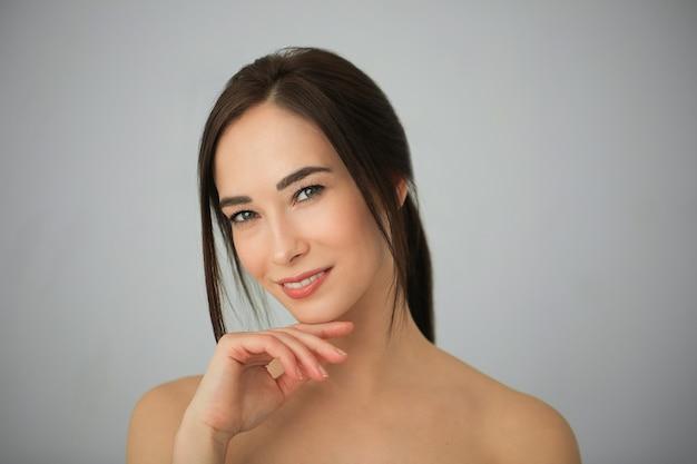 完璧な肌を持つ大人のブルネットの女性の肖像画。スキンケアのコンセプト