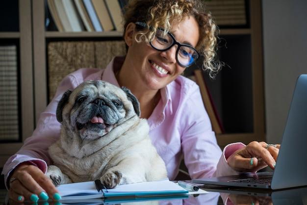 ホームオフィスルームのラップトップコンピューターで一緒に働く大人の陽気な若いきれいな女性と面白い犬の肖像画.-人々の概念とオンライン現代の仕事の活動