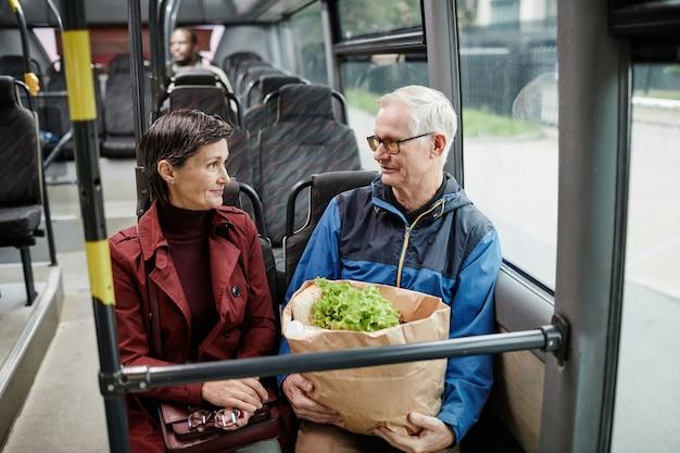Портрет взрослой пары, болтающей в автобусе во время поездки на общественном транспорте в городском копировальном пространстве