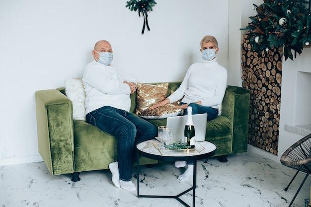 Портрет взрослой пары в масках на зеленом диване, используя ноутбук для празднования рождественских праздников.