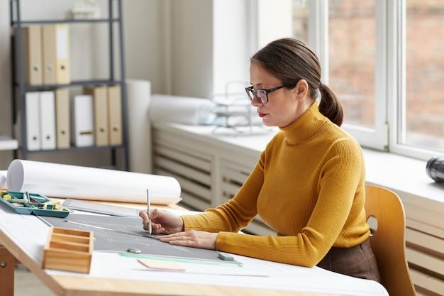 사무실에서 책상에서 작업하는 동안 청사진 및 계획을 그리기 성인 여성 건축가의 초상화,