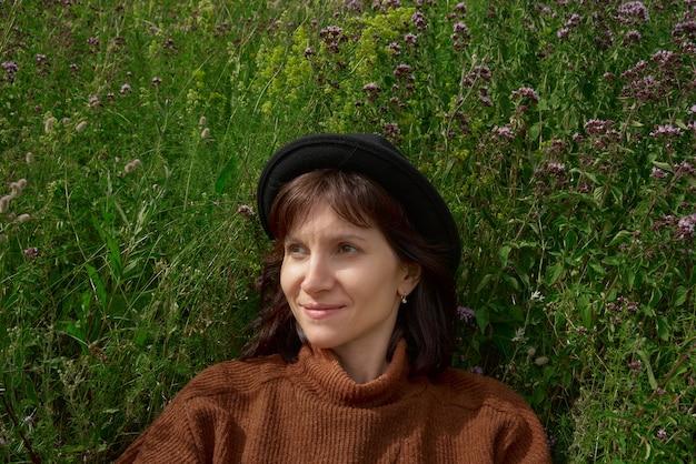 牧草地カレリアに座っている帽子の大人の女性の肖像画