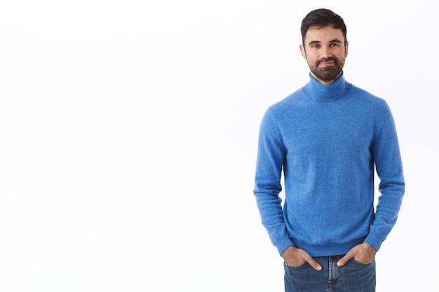 Портрет взрослого красавца с бородой, держась за руки в карманах джинсов, улыбаясь с дружелюбным беззаботным выражением лица, стоя у белой стены в повседневной нормальной позе