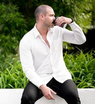 屋外でコーヒーを飲む大人の男性の肖像画