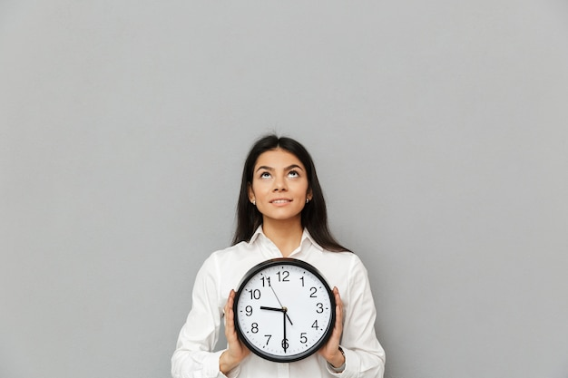丸い時計を保持していると灰色の壁に分離されたcopyspaceを上向きに見てオフィス服を着ている30代の大人の女性の肖像画