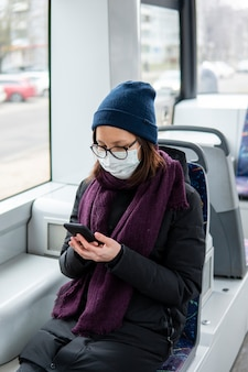 公共交通機関にサージカルマスクを身に着けている大人の女性の肖像画