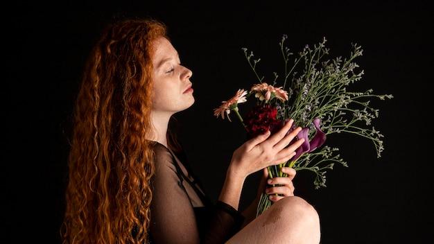 色とりどりの花を持つ大人の女性の肖像画