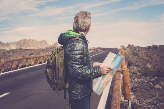 Портрет пожилого человека приключений с картой и снаряжением экстремального исследователя на горе с длинной прямой дорогой перед ним для долгой прогулки. страсть к путешествиям и путешествия концепции изображения. скалы и голубое небо живописные
