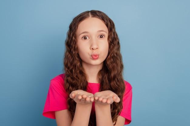 Портрет ласковой мечтательной красивой девушки, взявшись за руки, дует воздушный поцелуй на синем фоне