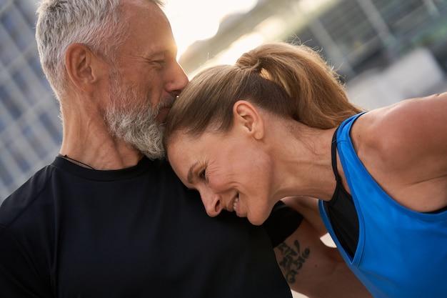 朝のトレーニングをしているスポーツウェアの愛情のこもった中年カップルの男性と女性の肖像画