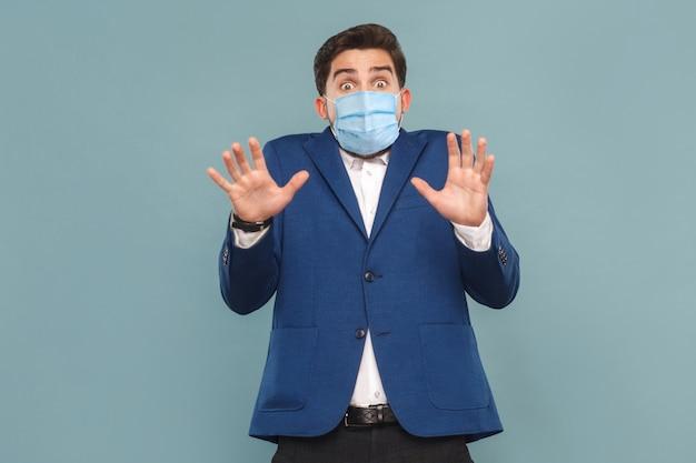 외과용 의료 마스크를 쓴 겁에 질린 젊은 남자의 초상화. 겁에 질린 상태로 카메라를 보고 있습니다. 얼굴 비즈니스 사람들이 의학 및 건강 관리 개념입니다. 파란색 배경에 실내, 스튜디오 촬영