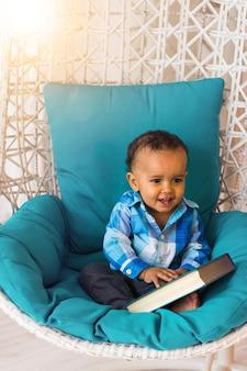 椅子に本を持っているアフリカ系アメリカ人の男の子の肖像画。