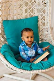 ソファに本を持っているアフリカ系アメリカ人の男の子の肖像画。