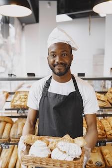パン屋で焼きたてのパンを持つアフリカ系アメリカ人のパン屋のポートレート。小さなペストリーを持つパティシエ。