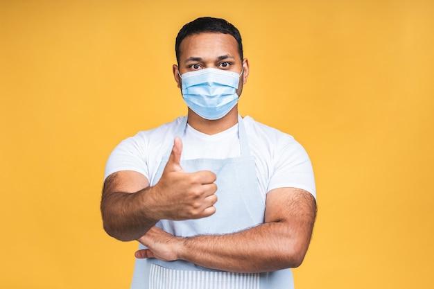 アフリカ系アメリカ人の黒人インド人シェフの肖像画または黄色の背景の聖霊降臨祭のコピースペース上に分離されたコロナウイルス予防のためのマスクで料理人。いいぞ。