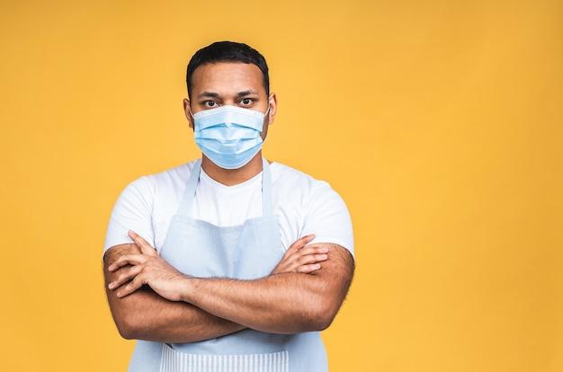 アフリカ系アメリカ人の黒人インド人シェフの肖像画または黄色の背景の聖霊降臨祭のコピースペース上に分離されたコロナウイルス予防のためのマスクで料理人。