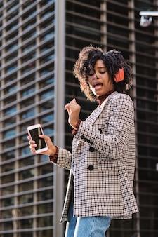 路上で屋外でヘッドフォンと携帯電話で音楽を聴いて楽しんでいるアフリカ系アメリカ人の実業家の肖像画。