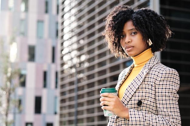 金融都市地区の屋外に立っている間コーヒーを保持しているアフリカ系アメリカ人の実業家の肖像画。