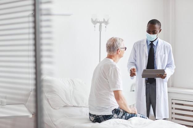 Портрет афро-американского врача разговаривает со старшим мужчиной в белой больничной палате, копией пространства