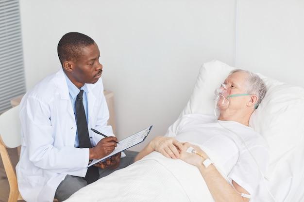 Портрет афро-американского доктора разговаривает со старшим мужчиной, лежащим на больничной койке с кислородной маской, копией пространства