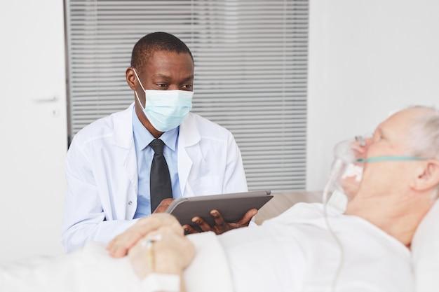Портрет афро-американского врача в маске во время разговора со старшим пациентом, лежащим на больничной койке, копией пространства