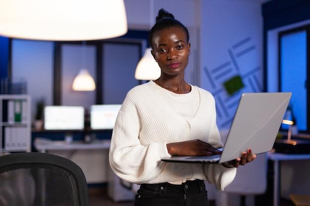 ラップトップコンピューターを保持しているアフリカ系アメリカ人のエグゼクティブマネージャーの肖像画