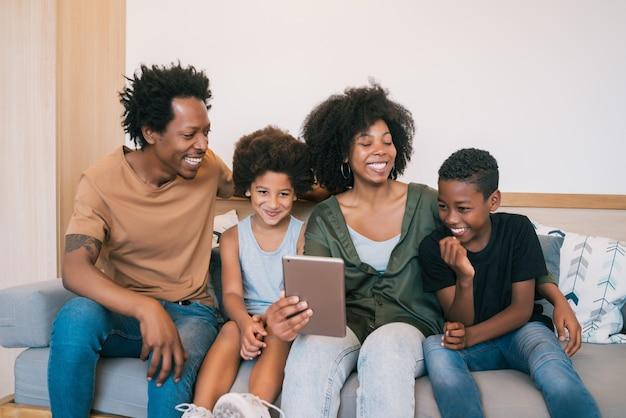 自宅でデジタルタブレットと一緒に自分撮りをしているアフリカ系アメリカ人の家族の肖像画。家族とライフスタイルの概念。